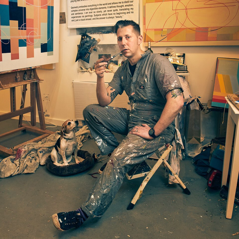Todd Brugman with some of his art, his beagle Maxine, and a pipe.